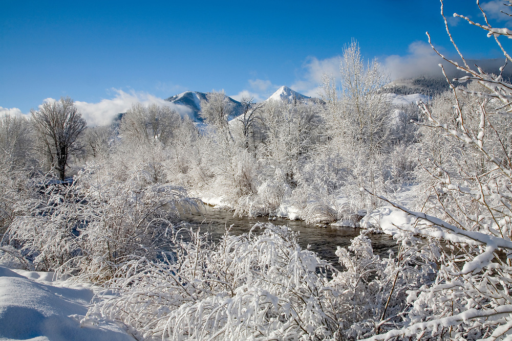 Fresh snow and lifting clouds frame Sun Valleys Baldy Mountain on a winters morning from the edge of the Wood River just north of Ketchum. Licensing and Open Edition Prints