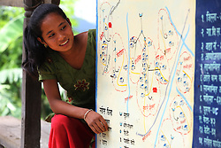 Auna Magar looks at a map of the water distribution system as part of the NEWAH WASH water project in Puware Shikhar, Udayapur District, Nepal.