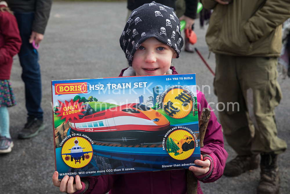 Uxbridge, UK. 1 February, 2020. A child holds a 'Boris HS2 train set' before attempting to deliver it with environmental activists from Stop HS2, Save the Colne Valley and Extinction Rebellion campaigning against the controversial HS2 high-speed rail link to the constituency office of Boris Johnson in Uxbridge during a 'Still Standing for the Trees' march from the Harvil Road wildlife protection camp in Harefield through Denham Country Park to three addresses closely linked to the Prime Minister in his Uxbridge constituency. Boris Johnson is expected to make a decision imminently as to whether to proceed with the high-speed rail line.
