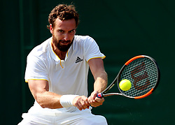 Ernests Gulbis in action against Juan Martin Del Potro on day four of the Wimbledon Championships at The All England Lawn Tennis and Croquet Club, Wimbledon.