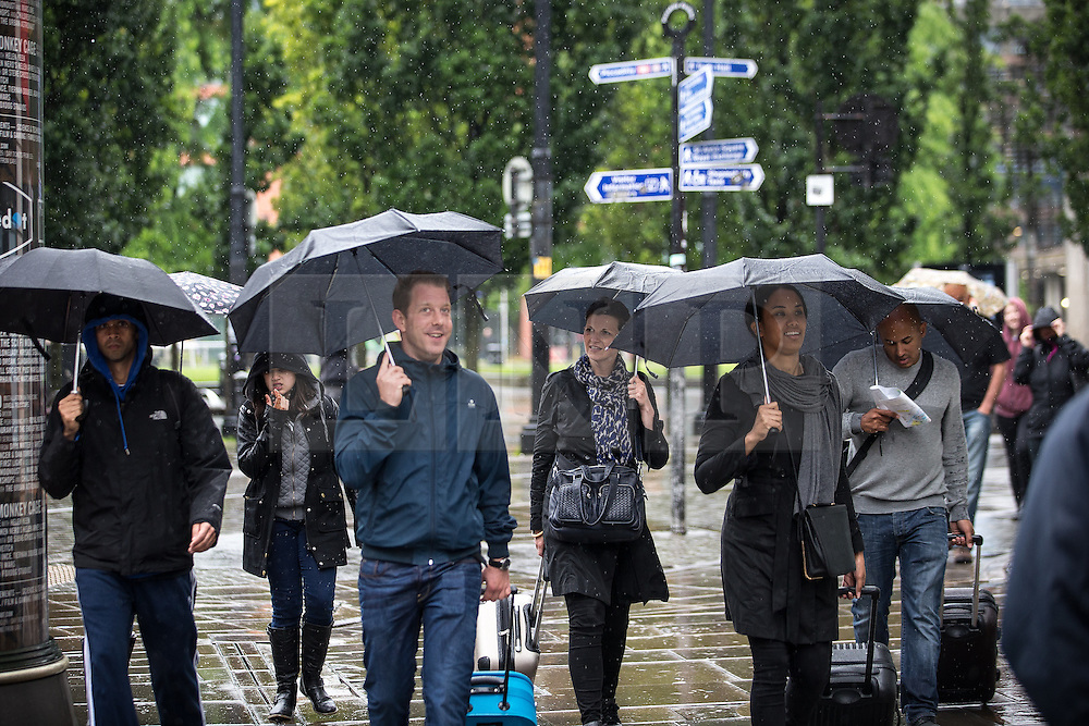© Licensed to London News Pictures . 09/07/2016 . Manchester , UK . People with umbrellas on Market Street in Manchester City centre as persistent , heavy rain leads to flooding of roads and tramways in Manchester City Centre . Photo credit : Joel Goodman/LNP