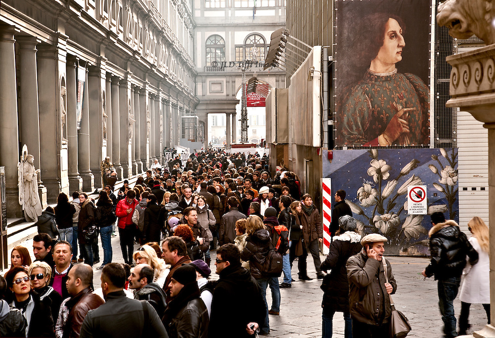 """Even in January, Florence was very crowded.  This view is from the Palazzo Vecchio along the Uffizi Gallery.  The crowd is a mix of tourists and residents, apparently.  Note the live """"sculpture"""" on the left.  We'll see him again later.  Banner showing a modern copy of a Renaissance portrait of a large-nosed man (Cosimo dei Medici?) hangs at right in advertisement for some feature on offer at the time."""
