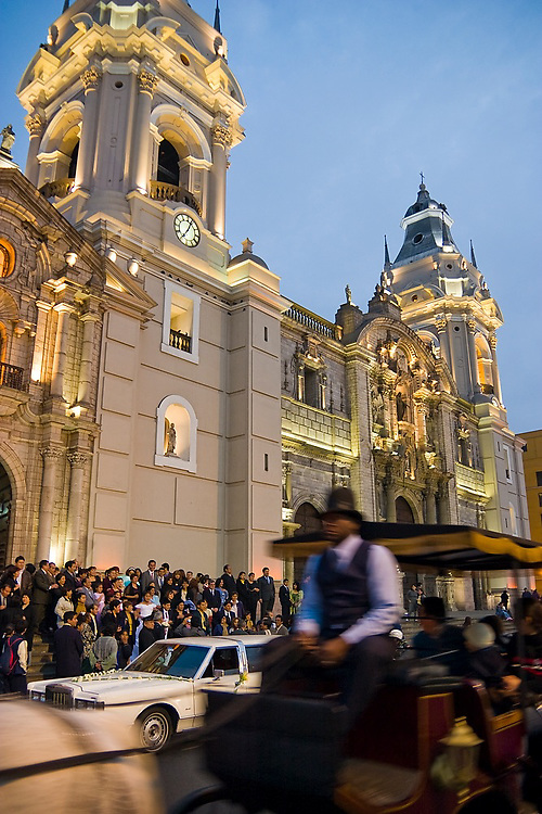 A wedding procession, including a cadillac limousine and a horse drawn carriage, passes in front of the Lima Cathedral as it circles the Plaza de Armas in Lima, Peru.