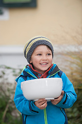 Little boy holding a bowl of salad and smiling, Bavaria, Germany