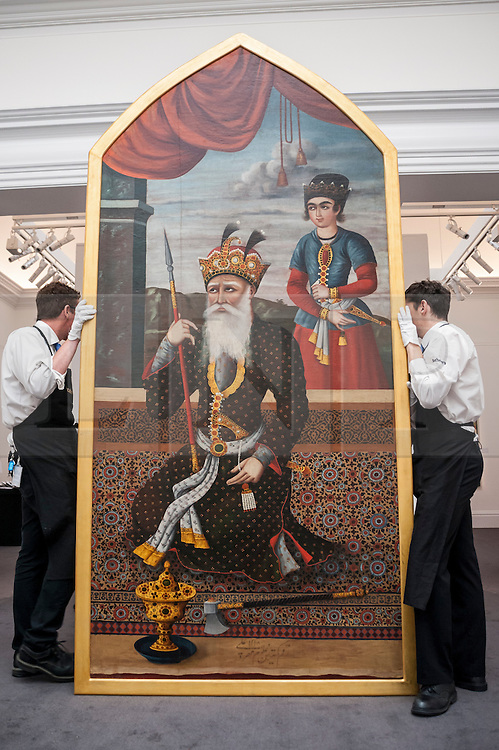 """© Licensed to London News Pictures. 02/10/2015. London, UK. Sotheby's technicians carry a """"Monumental Historical Qajar portrait of King Jamshid"""" (est. £250k - 350k) at the preview of Indian and Islamic Art Week at Sotheby's which runs from 2 to 7 October.  Photo credit : Stephen Chung/LNP"""