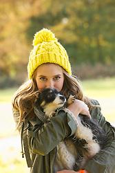 Teenage Girl Hugging Puppy Outdoors