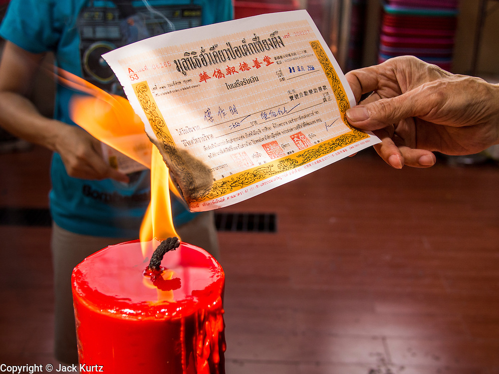 "26 AUGUST 2013 - BANGKOK, THAILAND: A man burns the receipt he received after donating a coffin to the Poh Teck Tung Foundation for Hungry Ghost Month in Bangkok. Burning the receipt, which is a form of Ghost Money, is a part of the ritual of donating coffins. Poh Teck Tung operates hospitals and schools and provides assistance to the poor in Thailand. The seventh lunar month (August - September in 2013) is when the Chinese community believes that hell's gate will open to allow spirits to roam freely in the human world for a month. Many households and temples will hold prayer ceremonies throughout the month-long Hungry Ghost Festival (Phor Thor) to appease the spirits. During the festival, believers will also worship the Tai Su Yeah (King of Hades) in the form of paper effigies which will be ""sent back"" to hell after the effigies are burnt.     PHOTO BY JACK KURTZ"