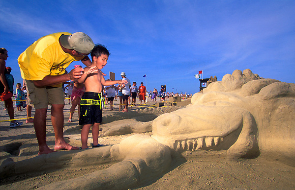 Stock photo of a father and son looking at a dragon sand castle on the beach at the AIA Annual Sandcastle Competition in Galveston