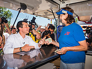 "13 AUGUST 2019 - DES MOINES, IOWA: PETE BUTTIGIEG pays for a ""pork chop on a stick"" he bought at the Iowa State Fair. Buttigieg, the Mayor of South Bend, Indiana, is running to be the Democratic nominee for the US presidency. He spoke at the Des Moines Register Political Soap Box at the Iowa State Fair and then toured the fairgrounds. Iowa has the first event of the presidential selection cycle. The Iowa Caucuses are February 3, 2020.               PHOTO BY JACK KURTZ"