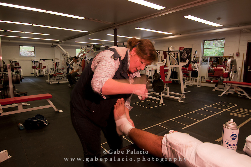 Trainer Sarah Yerkes tapes a student's ankle in the weight room of the Harvey School prior to a football game on October, 16, 2010.  (photo by Gabe Palacio)