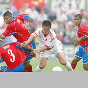 China's Moazhen Su gets through a tackle from Costa Rica's Luis Marin