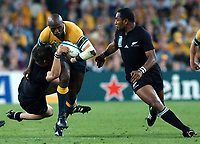 Photo. Steve Holland.Australia v New Zealand, Semi-final at the Telstra Stadium, Sydney. RWC 2003.<br />15/11/2003.<br />Wendell Sailor, second right is tackled with Joe Rokocoko right.