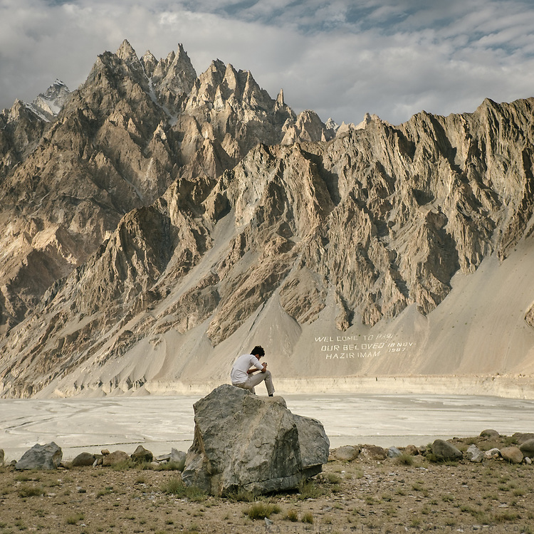 Above the village of Passu, a teenager checks his Facebook. Many residents here are Ismaili, followers of a moderate branch of Islam. A sign on the mountain slope commemorates the time in 1987, when the Ismaili imam, the Aga Khan, visited the remote region.