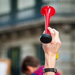 A protestor uses an air horn to make noise in a protest against social cuts and tax increases.