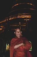 Yangon, Myanmar - November 15, 2011: A Burmese stands at night at the Shwedagon Pagoda in central Yangon.