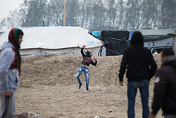 © Licensed to London News Pictures . 24/10/2016 . Calais , France . People play with a tennis ball in the Jungle migrant camp in Calais , Northern France , underway , on the day of a planned eviction and start of the destruction of the camp . Photo credit: Joel Goodman/LNP