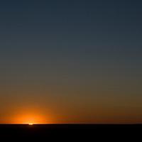 The sun rises over the vast horizon of the Gobi Desert in Mongolia.