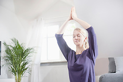 Young woman doing lotus pose yoga in living room, Bavaria, Germany