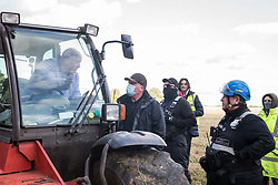 Aylesbury Vale, UK. 1st October, 2020. A farmer in a telehandler asks National Eviction Team bailiffs working on behalf of HS2 Ltd for clarification as to why they are erecting a fence across his field during the eviction of anti-HS2 activists from a wildlife protection camp in ancient woodland at Jones' Hill Wood. Around 40 environmental activists and local residents, some of whom living in makeshift tree houses about 60 feet above the ground, were present during the evictions at Jones' Hill Wood which had served as one of several protest camps set up along the route of the £106bn HS2 high-speed rail link in order to resist the controversial infrastructure project.