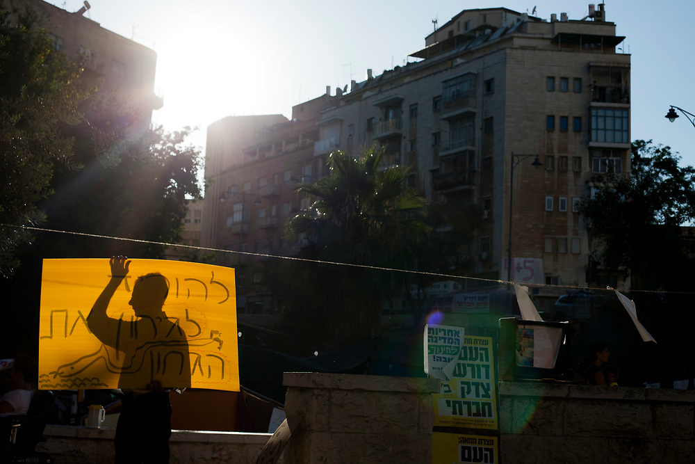 An Israeli protester holding a banner is silhouetted as he takes part in a demonstration against rising water rates, in central Jerusalem on August 7, 2011. Initially targeting soaring housing and property prices, the protests and marches of the last month in Israel quickly developed into a sweeping expression of rage against a wide array of social and economic issues.