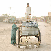 A donkey cart loaded with ice packs leaves an ice factory to sell ice throughout town. With regular rolling blackouts, failure, one way of cooling water is to simply use ice. An average day, it is 48 degrees C (119 F).