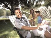 Two young girls attack their dad with a water hose while he reads the newspaper in a comfy chair