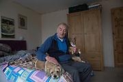 Ronald Cray, with dogs Mitch and Killy, at his home in Central Hill Estate on 18th June 2016 in South London, United Kingdom. Mr Cray has been a council tenant for 50 years and lived at Central Hill Estate for about two years. Central Hill is a low-rise estate of more than 450 homes in Crystal Palace in South London and has been recommended for demolition under Lambeth Council estate regeneration plan. The housing scheme, builtbetween 1966 and1974, was designed by Rosemary Stjernstedt under Lambeth Council's director of architecture,Ted Hollamby.