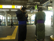 sumo wrestlers waiting at a train station Tokyo Japan