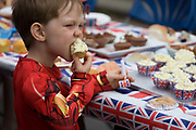 Boy enjoying home-made cakes at a neighbourhood street party in Dulwich, south London celebrating the Diamond Jubilee of Queen Elizabeth. A few months before the Olympics come to London, a multi-cultural UK is gearing up for a weekend and summer of pomp and patriotic fervour as their monarch celebrates 60 years on the throne and across Britain, flags and Union Jack bunting adorn towns and villages.