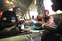 JON M. FLETCHER / The Times-Union -- 021510 -- Despite difficult circumstances, a group of medical evacuees from Port-au-Prince seem to find contentment in a game of cards inside one of the tents set up across the street from the Hospital Sacre Coeur to house the overflow of patients February 15, 2010. (Jon M. Fletcher, The Florida Times-Union)