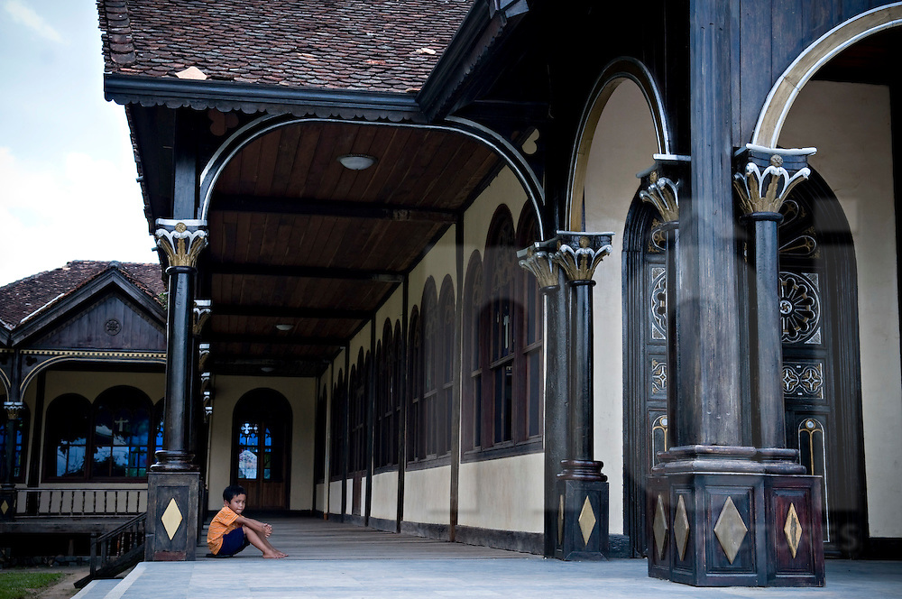 A young vietnamese boy sits under an arch of wooden Kontum catholic church, Vietnam, Southeast Asia