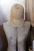 old dressing mannequin with cut on breast and a strawhat cap
