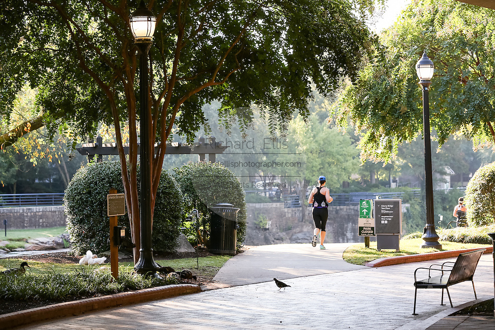 A runner along the Swamp Rabbit Trail and bike path in Falls Park on the Reedy River in downtown Greenville, South Carolina.