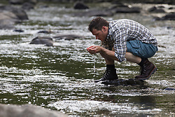 man in a river holding water in his hands