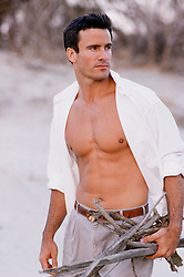 man with an open shirt gathering sticks on the beach