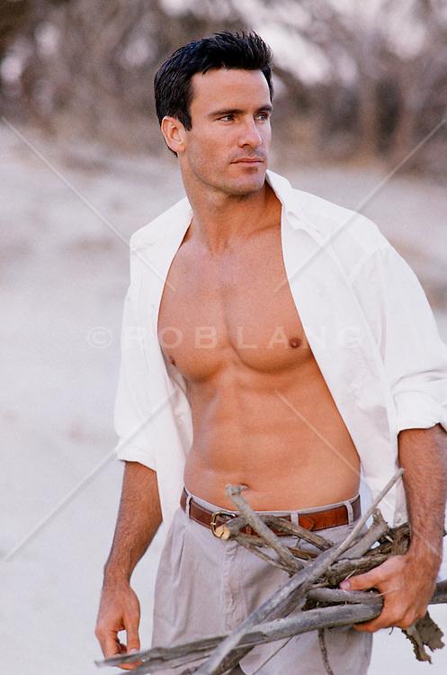 man with an open shirt gathering sticks on the beach