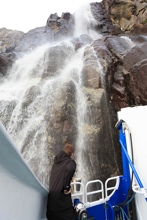 A man taking water from waterfall in Lysefjord, Norway.