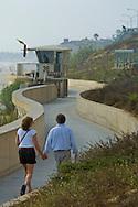 Couple walking along the seawall at Carlsbad State Beach, Carlsbad, San Diego, California