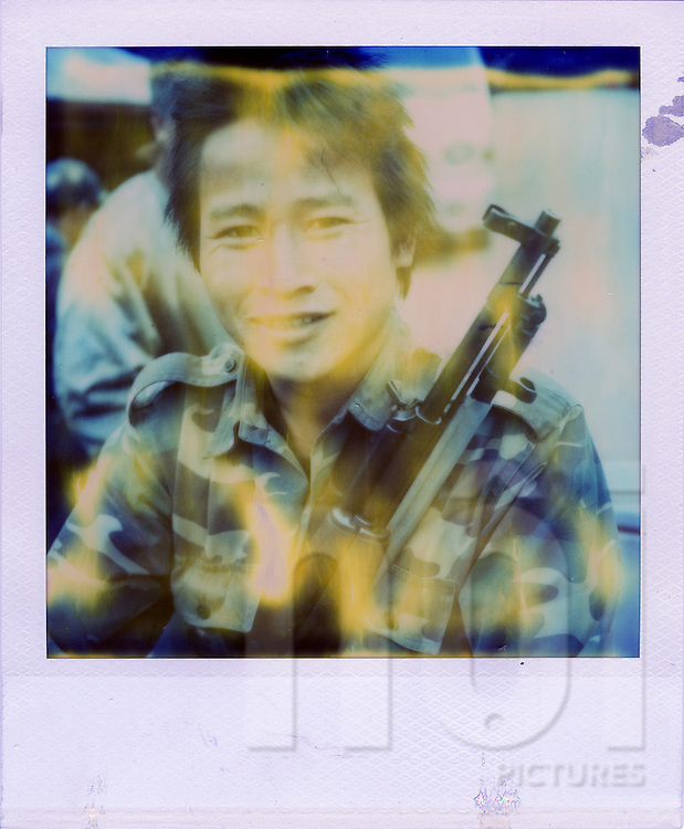 Portrait of a soldier holding an AK-47 gun in his hands and smiling at the camera, Laos, Southeast Asia