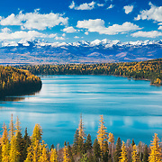 Scenic view of Holland lake, Swan valley, Swan mountain range and Mission mountains (aka the American Alps) from Holland Falls National Recreation Trail, northwest Montana.  Autumn colors of ponderous pine, red fir, and western larch frame the lake.  Published in Sunset western lifestyle magazine's Be Here Now travel feature, autumn 2014 issue, print and online editions. Finalist, Outdoor Photographer magazine's 2016 American Landscape competition. Featured in Outdoor Photographer print, digital and website advertisements for 2017 American Landscape competition (website ad continues). Willow Creek Press 2018 selection for Psalms calendar.