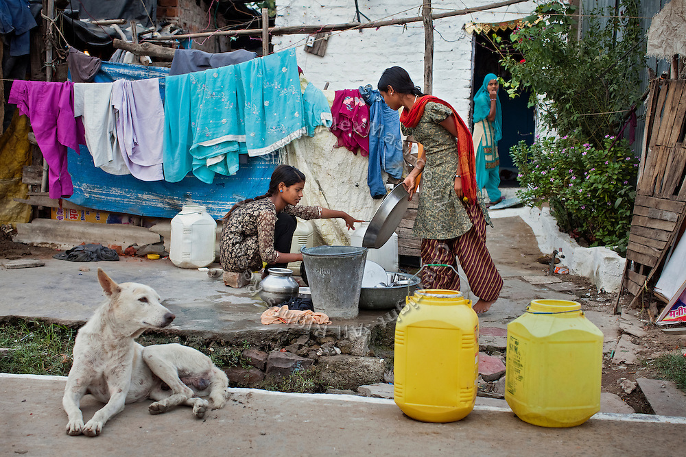 Next to her older sister Jyoti, 13, Poonam, 12, (right) is washing dishes in front of their newly built home in Oriya Basti, one of the water-contaminated colonies in Bhopal, central India, near the abandoned Union Carbide (now DOW Chemical) industrial complex, site of the infamous '1984 Gas Disaster'.