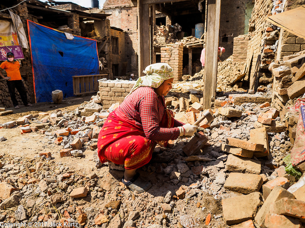 03 MARCH 2017 - BHAKTAPUR, NEPAL: A woman digs by hand through a home in Bhaktapur destroyed in the 2015 earthquake Bhaktapur, a popular tourist destination and one of the most historic cities in Nepal was one of the hardest hit cities in the earthquake. Recovery seems to have barely begun nearly two years after the earthquake of 25 April 2015 that devastated Nepal. In some villages in the Kathmandu valley workers are working by hand to remove ruble and dig out destroyed buildings. About 9,000 people were killed and another 22,000 injured by the earthquake. The epicenter of the earthquake was east of the Gorka district.      PHOTO BY JACK KURTZ