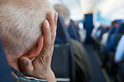elderly man in an airplane with his head resting on his hand