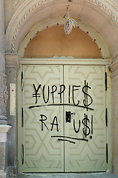 "Graffiti ""Yuppies Raus "" or ""Yuppies Out"" painted on door of renovated historic building in gentrified Prenzlauer Berg Berlin Germany"