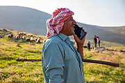 A Palestinian shepherd on a mobile phone with his herd of sheep in the Jordan River Valley, The Jordan Rift Valley, also Jordan Valley also called the Syro-African Depression, is an elongated depression located in modern-day Israel, Jordan, and Palestine. This geographic region includes the entire length of the Jordan River – from its sources, through the Hula Valley, the Korazim block, the Sea of Galilee, the (Lower) Jordan Valley, all the way to the Dead Sea,