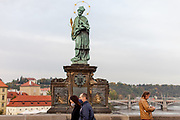 People - most of them wearing face masks - while passing Charles Bridge in Prague. As of 21st of October 2020 people have to wear face masks outside and inside.