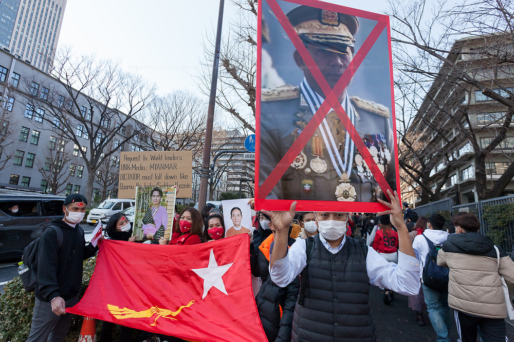 A man holds a crossed out poster of General Min Aung Hlaing, the nominal aleader of the military coup  as thousands of Japanese and Myanmar nationals protest outside the Japanese Foreign Ministry in Tokyo calling for the Japanese government to take action over the recent coup in Myanmar. Kasumigaseki, Tokyo, Japan. Wednesday February 3rd 2021, Many of the protesters held flags of Aung San Suu Kyi's National League for Democracy (NLD), along with portraits of the the detained leader herself and former President, Win Myint.