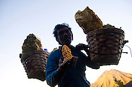A sulphur miner shows a piece of sulphur for sale at the Kawah Ijen Sulphur Mines in East Java, Indonesia, Southeast Asia