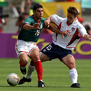 Mexico's Salvador Carmona tackled by USA's Josh Wolff