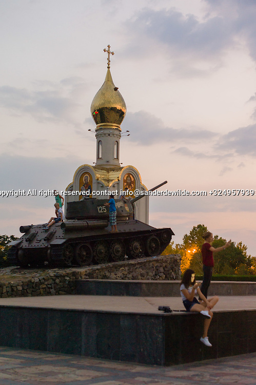 """20150829  Moldova, Transnistria,Pridnestrovian Moldavian Republic (PMR) Tiraspol. At the bank of the Dniestr River –<br /> along the """"25th October Street"""" – opposite<br /> the parliament building with the statue of<br /> Lenin is the """"Monument Square"""" with a<br /> Soviet T-34 tank, Kids play on their smartphone at sundown. An Russian Orthodox church stands beside the tank."""